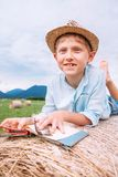 Boy with book lies on the hay roll Stock Photos