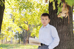 Boy with book looking sideways Stock Photos