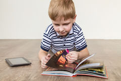 Boy with a book. Boy lying on the floor and reading a book stock photography