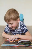 Boy with a book. Boy lying on the floor and reading a book royalty free stock image