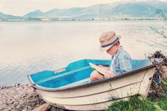 Boy with book seats in old boat on the lake bank Royalty Free Stock Images