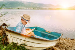 Boy with book seats in old boat on the lake bank Royalty Free Stock Photos