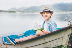 Boy with book sits in old boat on the mountain lake bank Stock Photo