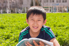 Boy and book. Boy sitting near the school and reading a book Royalty Free Stock Photos