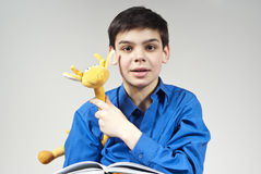 Boy with a book and toy. In the background Stock Photos