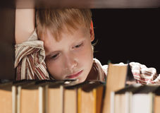 The boy at a bookcase gets the book. Stock Images