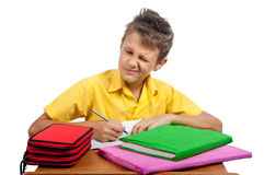 Boy with books makes a grimace. All on white background. Royalty Free Stock Image