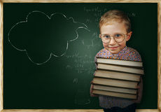 Boy with books near school chalkboard Royalty Free Stock Images