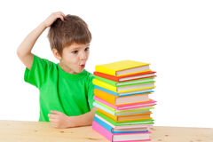 Boy with books scratching his head Royalty Free Stock Image