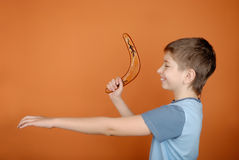 Boy with a boomerang. On an orange background Royalty Free Stock Image