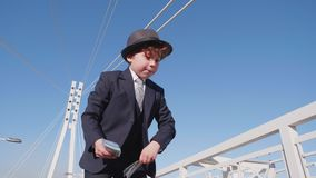 Boy boss waste American banknotes throw money. Funny little caucasian child toss wad cash fling bridge background. Kid businessman role play classical suit stock footage