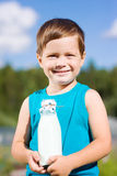 Boy with bottle of milk in summer Stock Photos