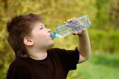 Boy with a bottle of water in nature Stock Images