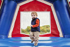Boy in bounce house. Toddler boy jumping inside a bounce house Royalty Free Stock Images