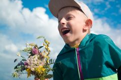 The boy with a bouquet against the sky. The boy with a bouquet laughs, explosion of emotions stock photography