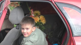 Boy with a bouquet  sits in car stock video