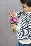 A boy with a bouquet of small pink roses in his hands. concept greetings for mother`s day, stock photo