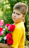Boy with bouquet in summer park Royalty Free Stock Photography