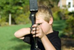 Boy With Bow and Arrow. Young boy with a bow and arrow learning to shoot royalty free stock photos