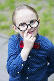 Boy with bow tie and big glasses is picking his nose Stock Image