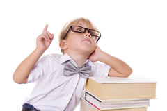 Boy with bow-tie and glasses sitting on books having idea Royalty Free Stock Images