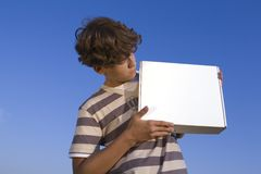 Boy with box. Young person with box in hand. Blue background Royalty Free Stock Image
