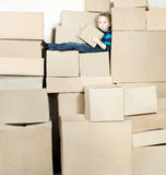 Boy with box sitting on heap boxes Royalty Free Stock Photos
