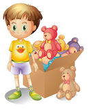A boy beside a box of toys Stock Photos