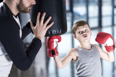 Boy boxer practicing punches with coach. Young boy boxer practicing punches with coach Royalty Free Stock Images