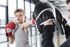 Boy boxer practicing punches with coach. Young boy boxer practicing punches with coach Royalty Free Stock Photo
