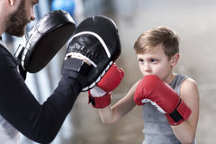 Boy boxer practicing punches with coach. Young boy boxer practicing punches with coach Royalty Free Stock Photography