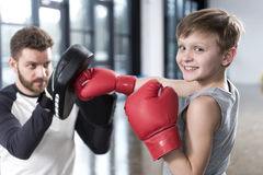 Boy boxer practicing punches with coach. Young boy boxer practicing punches with coach Stock Photo