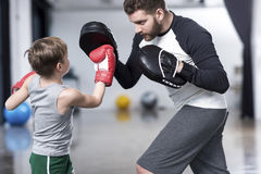 Boy boxer practicing punches with coach. Young boy boxer practicing punches with coach Stock Photography