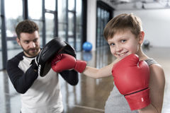 Boy boxer practicing punches with coach. Young boy boxer practicing punches with coach Royalty Free Stock Image