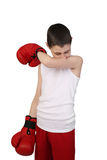 Boy boxer. Boy in sleeveless shirt and boxing gloves wipes nose isolated on white background - young boxer royalty free stock image