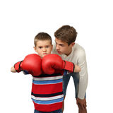 Boy boxer with trainer. Teenage boy helps his little brother in boxing gloves to prepare for a fight isolated on square white background Royalty Free Stock Photos