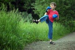 Boy-boxer trains in park stock photos