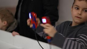 Boy boxing with gamepad in hands. Kid remote controlling robot. Boy fighting with controller game. Boy using gaming controller. Boy playing remote control toy stock footage