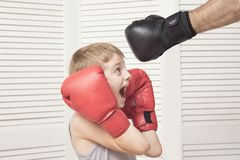 Boy in boxing gloves fights with a man`s hand in a glove. Boy in boxing gloves fights with a man`s hand in a glove stock photography