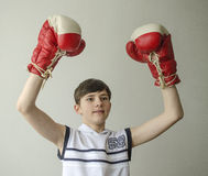 Boy in boxing gloves with raised hands in victory gesture Royalty Free Stock Images