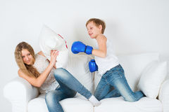 Boy in boxing gloves shoots girl Stock Photos