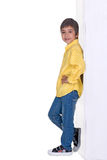 The boy the boy stands  and smiles. The boy stands having leaned the elbows to a wall and smiles Royalty Free Stock Images