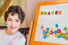 Boy with braces and magnetic letters Stock Image