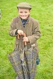 Boy at Braemar Royal Highland  Gathering. Portrait of boy wearing kilt, tweeds and flat cap and holding umbrella  attending Braemar Royal Highland Gathering held Royalty Free Stock Photo