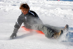 Boy Braking the Sled While Sledding Down the Hill. With snow background Stock Photography