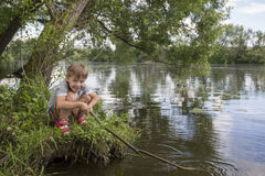 Boy with the branch in the hands. Likable merry boy with the branch in the hands sits on the shore in the water and it smiles stock image
