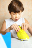 Boy with brand new yellow footbal boot Stock Photography