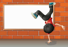 A boy breakdancing in front of the empty board Royalty Free Stock Photography