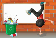 A boy breakdancing near a trash can with an empty board Stock Photography