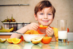 Boy, breakfas. T, drinks milk, eats cereal and orange Royalty Free Stock Photography